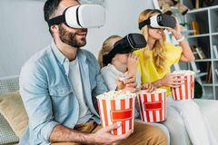 excited young family in virtual reality headsets watching movie with buckets royalty free stock image