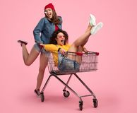Cheerful young woman pushing shopping cart with friend royalty free stock photos