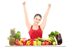 Excited young female gesturing happiness on a table full of frui Stock Photos