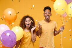 Excited young friends couple african american guy girl in casual clothes isolated on yellow background. Birthday holiday