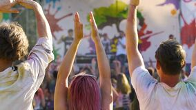Excited young friends dancing, waving hands at open air music festival, slowmo