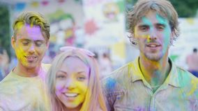 Excited young friends having fun at color festival, smiling and posing to camera. Stock footage stock footage