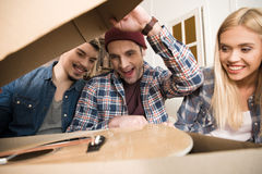 Excited young friends opening box with guitar. Close-up view of excited young friends opening box with guitar Royalty Free Stock Photos