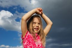 Excited Young Girl against Cloudy Sky Royalty Free Stock Images
