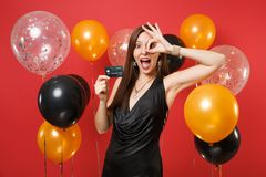 Excited young girl in black dress celebrating, holding credit card and showing OK sign on red background air balloons royalty free stock photos