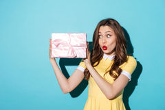 Excited young girl in dress looking at a present box Royalty Free Stock Images
