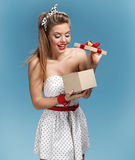 Excited young girl opening present box. Set photos of beautiful young retro pinup woman on blue background Stock Photos