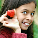 Excited young girl showing  juicy red strawberry. Stock Photography