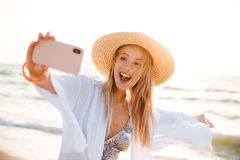 Excited young girl in summer hat and swimwear. Spending time at the beach, taking a selfie with outsretched hand Stock Photography