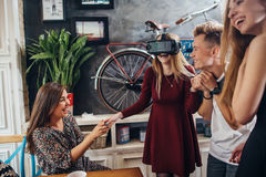 Excited young girl testing virtual reality headset while her friends watching, laughing and supporting her. Group of. Teenagers having fun time together indoors Stock Photography