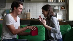Excited young girlfriend receiving gift from boyfriend at home stock video