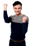 Excited young guy with clenched fists Stock Images
