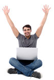 Excited young guy with laptop. Guy with laptop on his lap, raising arms up Royalty Free Stock Photo