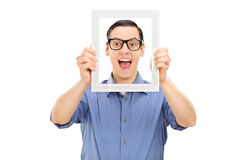 Excited young guy posing behind a picture frame Royalty Free Stock Photo