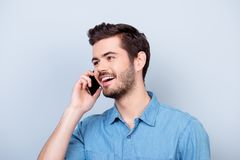 Excited young handsome boy is talking on his smartphone and smiling. He is wearing jeans shirt and behind him is a pure blue back royalty free stock photography