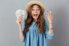 Excited young happy woman holding money. Looking camera. Stock Photo