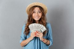 Excited young happy woman holding money. Looking camera. Royalty Free Stock Images