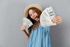 Excited young happy woman holding money. Looking camera. royalty free stock image