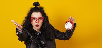 Excited young hipster girl holding alarm clock, isolated on yellow background. Copy space. Woman in black leather jacket and glass royalty free stock images