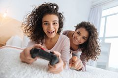 Excited young ladies in casual playing video games Stock Photo