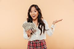 Excited young lady with long dark hair holding fan of 100 dollar. Bills expressing gladness, having a lot of money over peach background stock photography