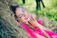 Excited young lady in pink dress relaxing on hay Stock Images