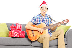 Excited young male with christmas hat seated on sofa playing an Stock Images