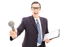 Excited young male interviewer in suit holding microphone. Isolated on white background stock photography
