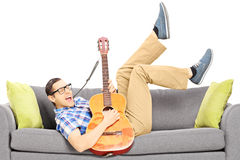 Excited young male lying on a modern couch and playing a guitar Stock Photos