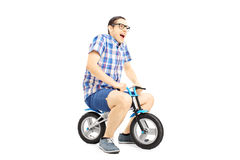 Excited young male riding a small bicycle Stock Photo