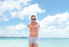 Excited young man in bathing suit pointing. To the camera while standing on the beach Royalty Free Stock Images