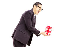 Excited young man in black suit giving a present Stock Photo
