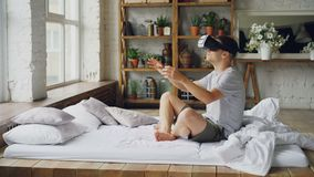 Excited young man is using augmented reality glasses moving hands while sitting on double bed in light apartment. Modern. Excited young man in casual clothes is stock footage