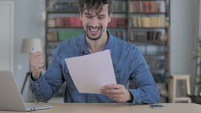 Excited Young Man Celebrating  Success After Reading Documents, New Contract stock footage