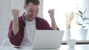 Excited Young Man Celebrating Success, Working on Laptop stock footage