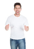 Excited Young Man With Clenching Fists. Portrait of excited young man with clenching fists isolated over white background Royalty Free Stock Images