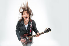 Excited young man with electric guitar shouting and shaking head. Excited young man in black leather jacket with electric guitar shouting and shaking head over royalty free stock photos