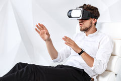 Excited young man is getting experience using VR-headset glasses of virtual reality gesticulating with his hands Royalty Free Stock Photography