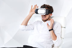 Excited young man is getting experience using VR-headset glasses of virtual reality gesticulating with his hands Royalty Free Stock Image