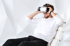 Excited young man is getting experience using VR-headset glasses of virtual reality gesticulating with his hands Stock Photos
