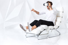 Excited young man is getting experience using VR-headset glasses of virtual reality gesticulating with his hands Stock Photo