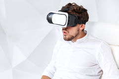 Excited young man is getting experience using VR-headset glasses of virtual reality gesticulating with his hands Stock Photography