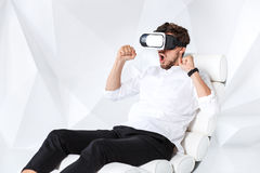 Excited young man is getting experience using VR-headset glasses of virtual reality gesticulating with his hands Royalty Free Stock Images