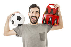 Excited young man holding ball and pack of beer Stock Photo