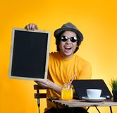 Excited Young Man Holding Empty Blackboard While Working on Summ. Er Vacation Season Against Yellow Background Stock Photography