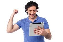 Excited young man holding touch pad device Stock Images