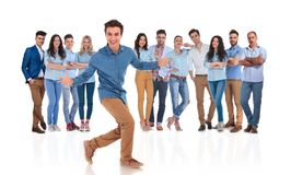 Excited young man invites you in his casual group. Excited young men invites you in his casual group with an energetic hand gesture while standing on white royalty free stock images