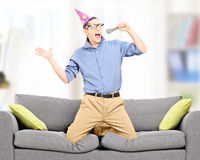 Excited young man with party hat singing on a microphone Royalty Free Stock Photos