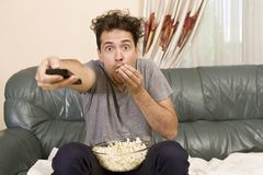 Excited young man with the remote and popcorn on the couch watching tv royalty free stock photography
