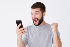 Excited young man screaming on his mobile phone. Close-up shot of excited young man screaming on his mobile phone over white background Stock Images